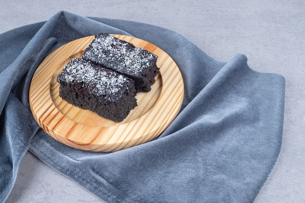 Wooden plate of sliced brownie cakes on stone table