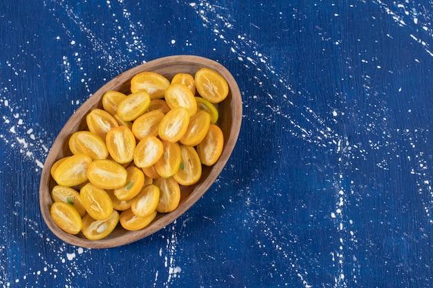 Piatto di legno di frutti di kumquat a fette su una superficie di marmo.