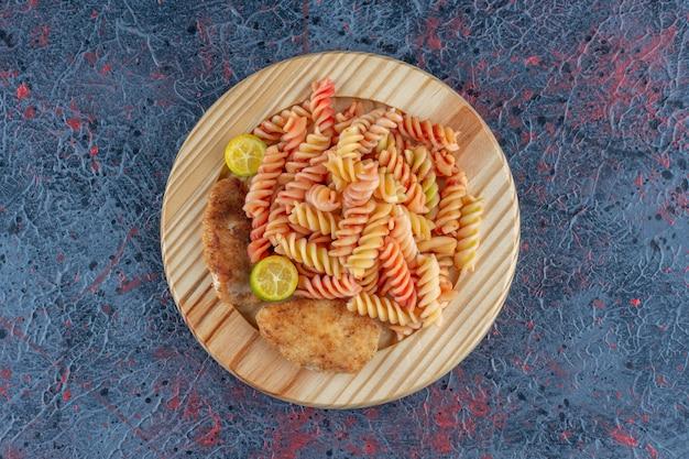 Un piatto di legno di maccheroni a spirale con carne di coscia di pollo.