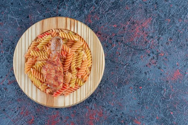 Un piatto di legno di maccheroni a spirale con carne di coscia di pollo