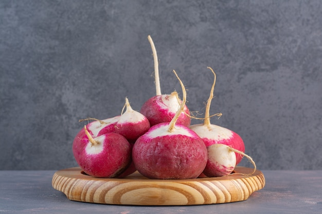 Wooden plate of summer harvested red fresh radishes on stone surface