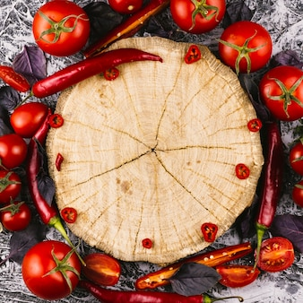 Wooden plate surrounded by chilli peppers and tomatoes