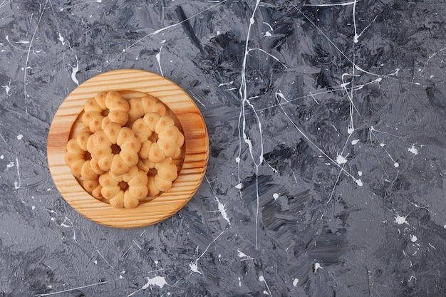 Wooden plate of sweet flower shaped cookies on marble background.