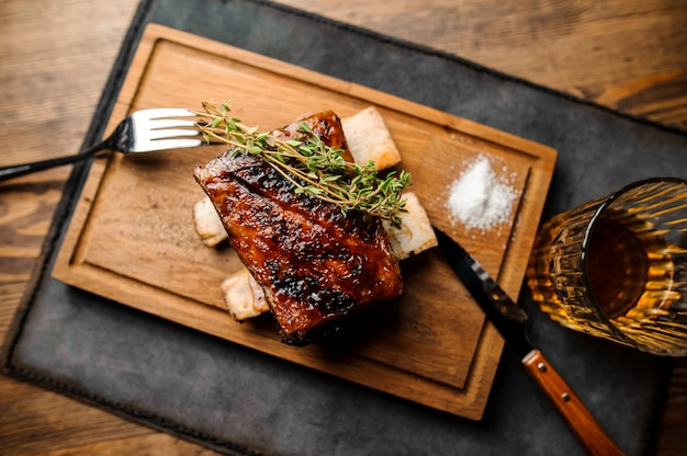 Wooden plate of tasty grilled rib with golden crust