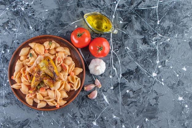 Piatto di legno di gustosa pasta di conchiglie con ala di pollo su superficie di marmo.