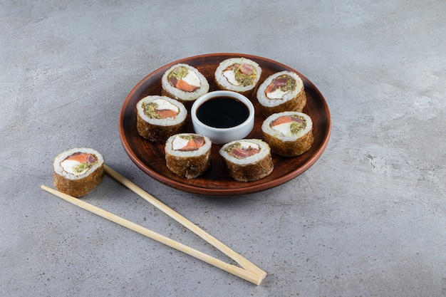 Wooden plate of tasty sushi rolls on stone background.