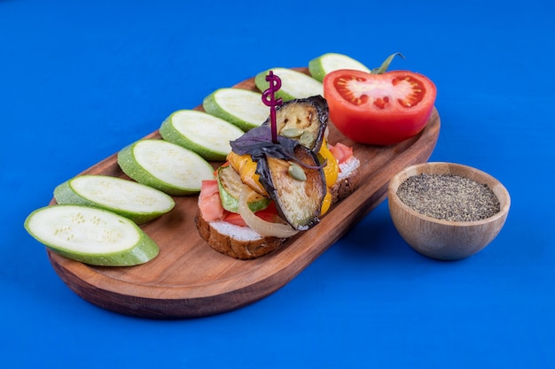 Wooden plate of tasty toast with vegetables and zucchinis on blue surface