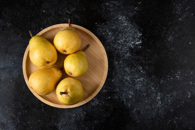 Piatto di legno di gustose pere gialle sulla superficie nera.