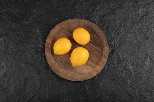 Wooden plate of three fresh lemons on black table.