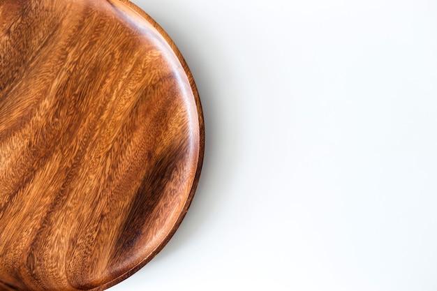 Вид сверху деревянной тарелки на белом столе.