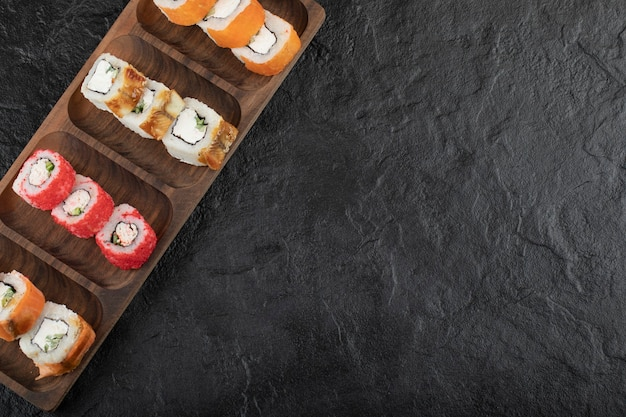 Wooden plate of traditional sushi rolls on black table