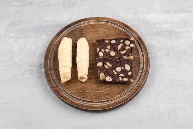 Piatto di legno di mutaki dolce tradizionale e biscotti al cacao sul tavolo di pietra.