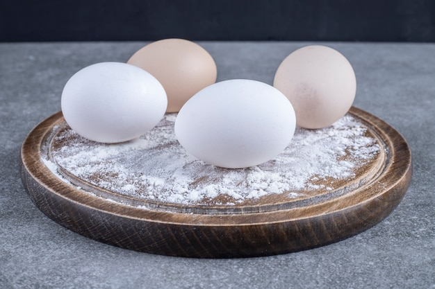 Wooden plate of white and brown chicken eggs with flour placed on stone table .