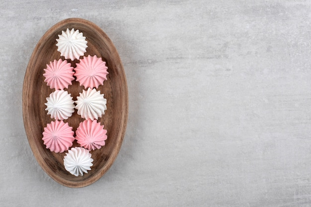 Piatto di legno di dolci meringa bianchi e rosa sul tavolo di pietra.