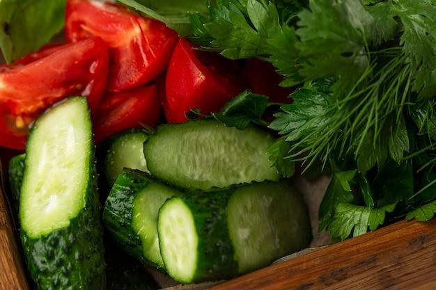 허브와 야채를 많이 넣은 나무 접시. 토마토 오이. 파슬리와 딜. 확대. 자연에서 온 채식주의, 비타민, 건강.