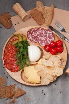 Деревянная тарелка с ассорти колбас и сыров