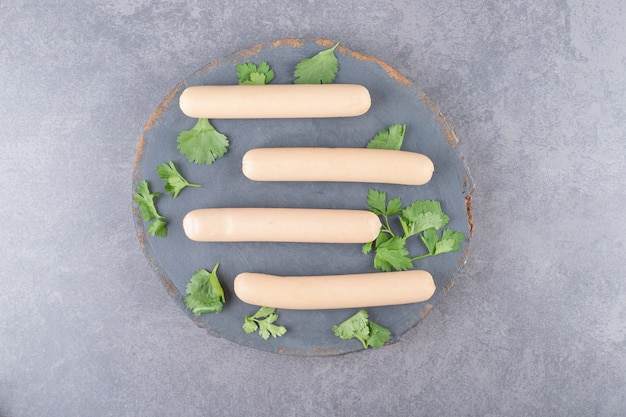 Un piatto di legno con salsicce bollite e prezzemolo