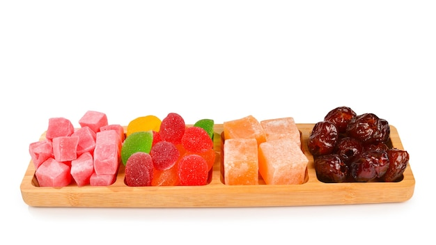 Wooden plate with cashew, marmalade and sweet turkish delight. isolated on white surface. space for text or design.