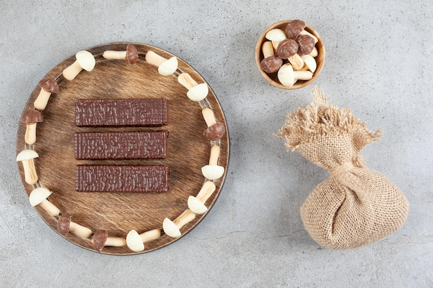 A wooden plate with chocolates and wooden bowl with sweet mushrooms