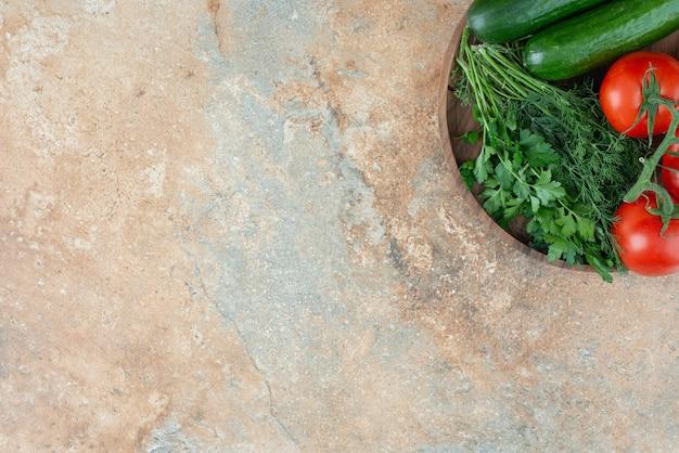 Un piatto di legno con cetrioli, verdure e pomodori.