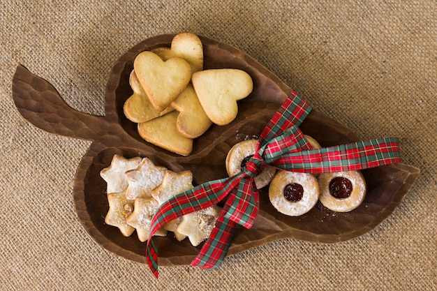 Wooden plate with different cookies on table