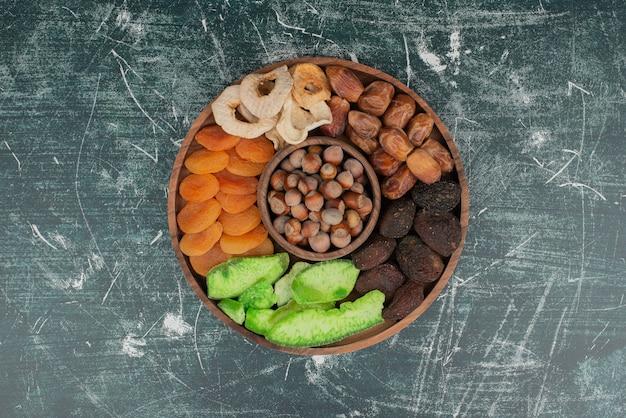Piatto di legno con frutta secca sul tavolo di marmo