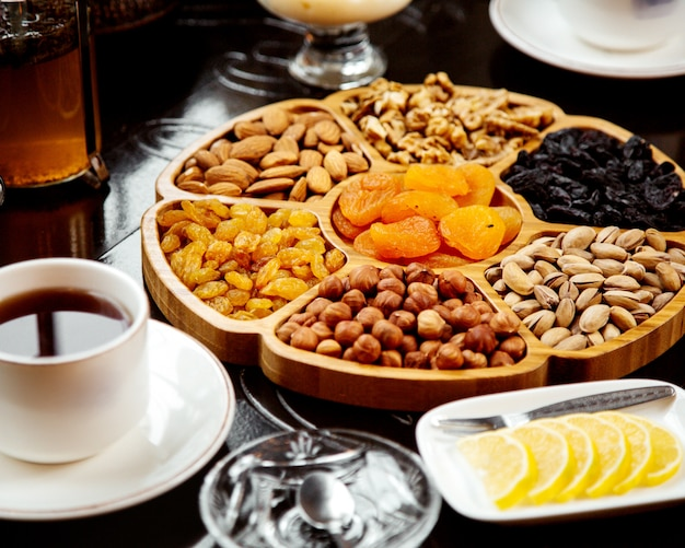 Wooden plate with dried fruits and nuts