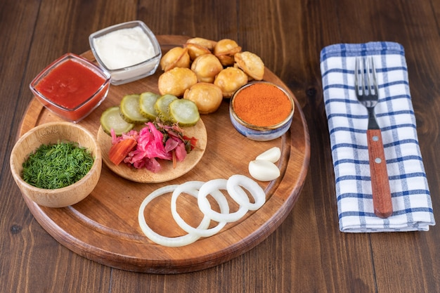 Wooden plate with fried dumplings, ketchup and pickles on wooden surface.