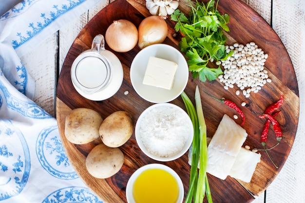 Деревянная тарелка с ингредиентами из рыбы и овощей для приготовления котлет с картофельным пюре.