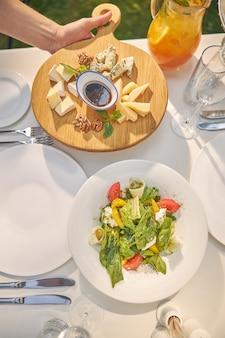 Деревянная тарелка с миксом сыра и белая тарелка с зеленым салатом от опытного шеф-повара
