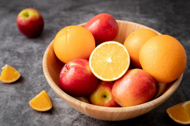 Wooden plate with orange and apple fruit on kitchen table.