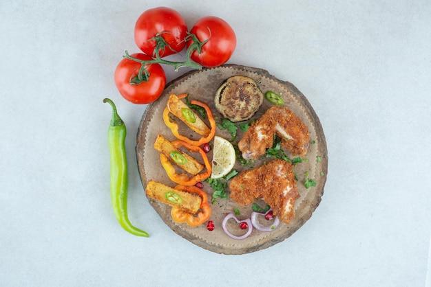 Un piatto di legno con peperoni e pomodori sul tavolo bianco.