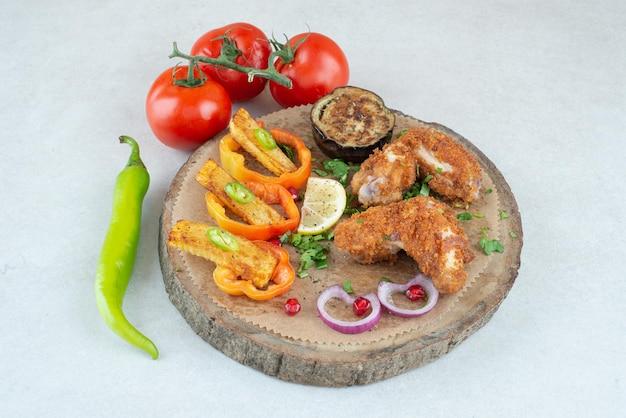 Un piatto di legno con peperoni e pomodori su bianco