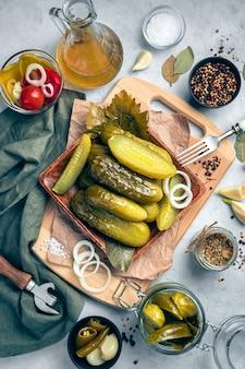 Деревянная тарелка с солеными огурцами на сером фоне с луком, чесноком, лавровым листом и специями. вертикальный вид.