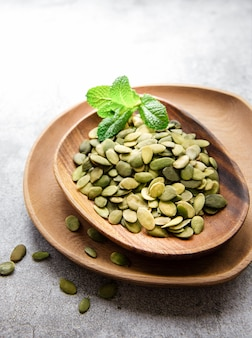 Wooden plate with pumpkin seeds on a gray concrete surface