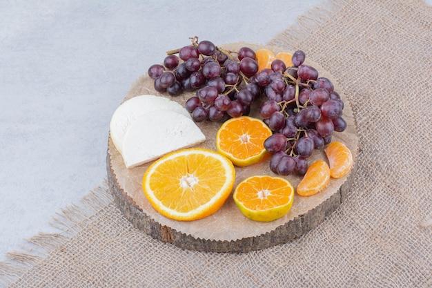 Un piatto di legno con formaggio a fette e frutta. foto di alta qualità