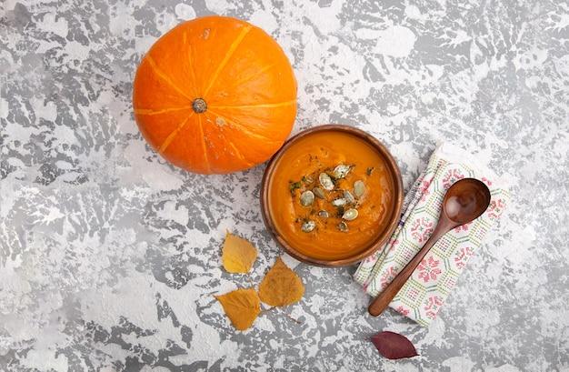 素朴なテーブルの上に木のスプーンで種をまぶしたスープカボチャのピューレと木のプレート。健康的なダイエット。