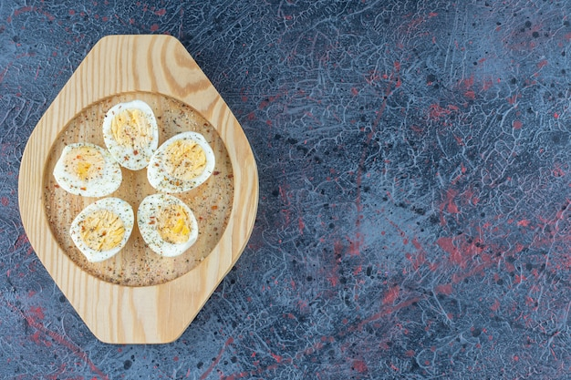 A wooden plate with spices hard boiled eggs .