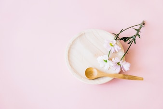 Wooden plate with spoon and flower