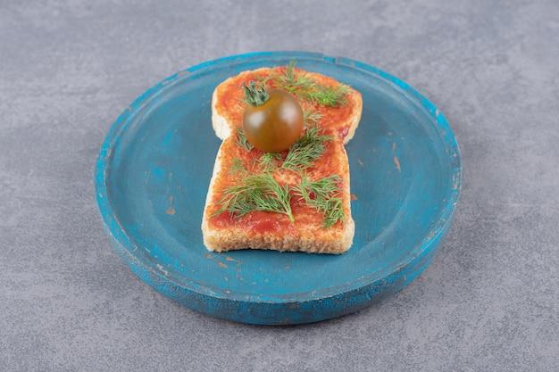 Un piatto di legno con pane tostato su uno sfondo di marmo.