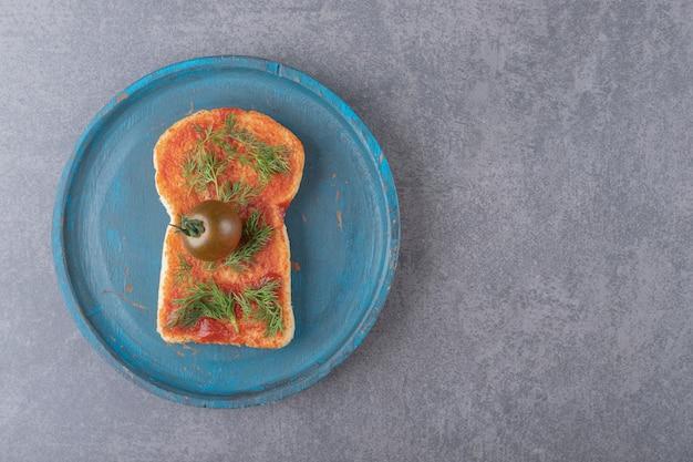 Un piatto di legno con pane tostato su una superficie di marmo