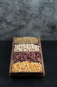 Piatti di legno con fagioli crudi e popcorn su fondo nero.