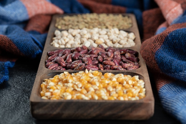 Piatti di legno con fagioli crudi e popcorn su un buio