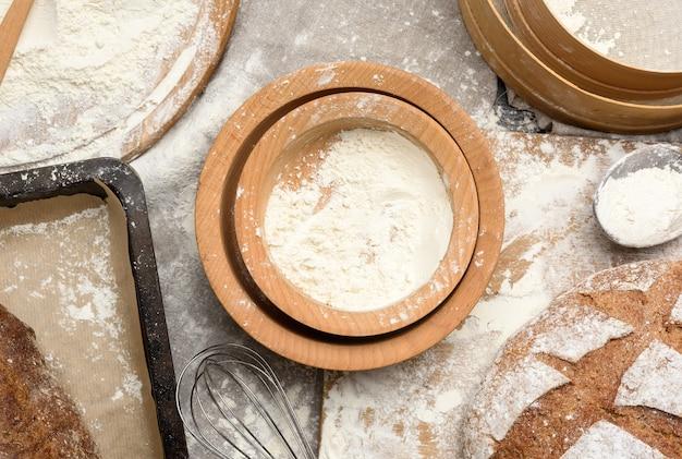 Деревянные тарелки с остатками белой пшеничной муки, вид сверху