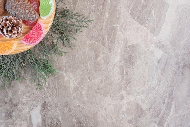 Piatto in legno di marmellate intorno a pigne e focaccina a mezzaluna ripiena di noci su marmo.
