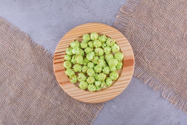 Деревянное блюдо на кусках ткани, на мраморном фоне держится небольшая куча засахаренного попкорна. фото высокого качества