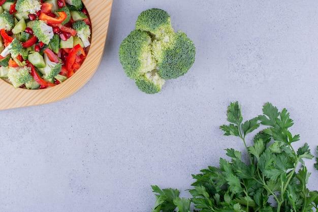 Piatto in legno di insalata con fasci di broccoli e foglie di prezzemolo su fondo marmo. foto di alta qualità