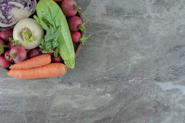 Wooden platter stocked with carrots, squash, turnips, red cabbage and turnip greens on marble.