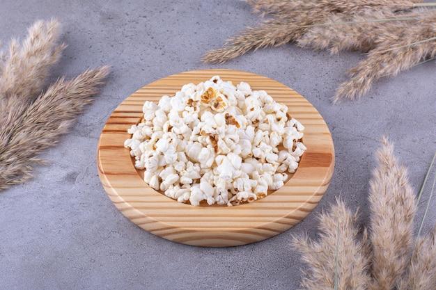 Деревянное блюдо с порцией попкорна на мраморном фоне посреди сушеной хвойной травы. фото высокого качества