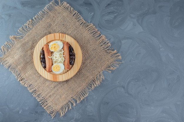 Wooden platter with sausages, sliced eggs, grated cheese and black olives on a piece of fabric on marble table.